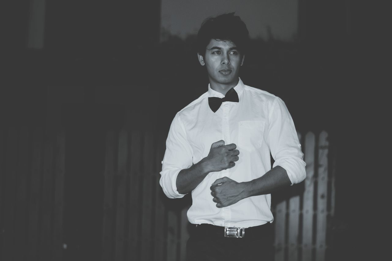 Man standing in bow tie at dusk