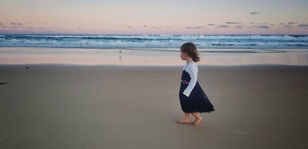 Full length of girl walking on shore at beach
