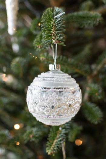 Single Ornament Hanging From A Christmas Tree Beautiful Christmas Green Color Hanging Holiday Isolated Lights Ornament Tree Ball Branch Card Delicate Focus On Foreground Glass Greetings Merry One Person Round Seasons Single White