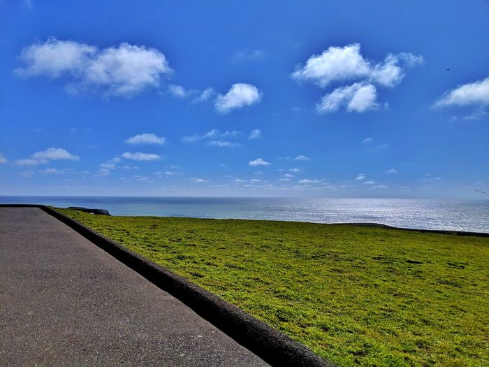 On the diagonal. Pavement, green grass, ocean, blue cloudy sky. Minimalism Green Grass Berm Pavement Asphalt Diagonal Blue Cloud Sky LINE Simple Edge Ocean Soil Dirt Contrast Therapeutic Zen Angled Overlook Pull Out Water Rural Scene Sea Sky Cloud - Sky Landscape
