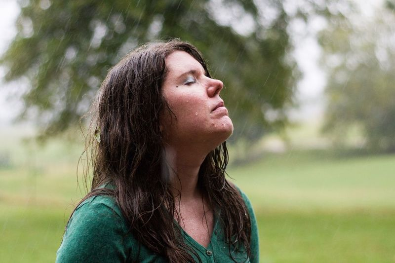 Close-Up Of Young Woman With Eyes Closed Standing On Field During Rainy Day