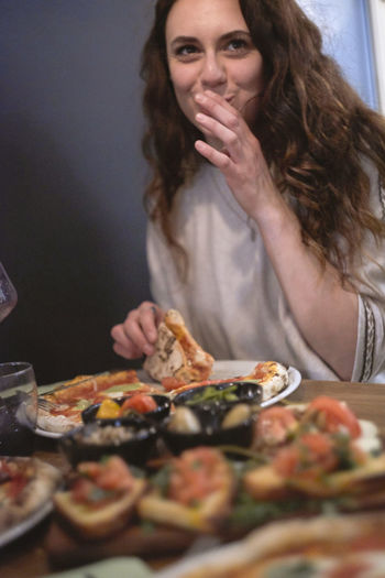 Young woman having pizza at food in restaurant