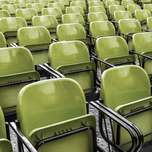 Full frame shot of empty green chairs at stadium