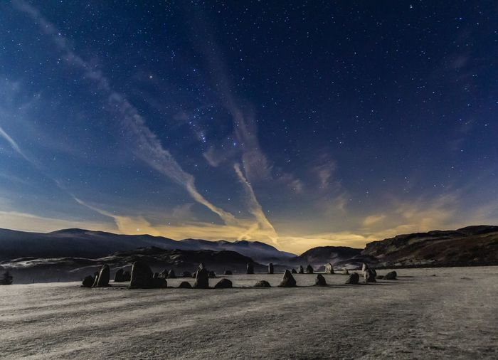 Scenic view of a stone circle in a mountainous landscape against sky at night