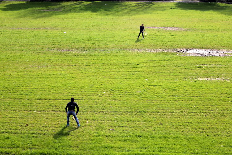 High angle view of friends playing tennis on grassy field