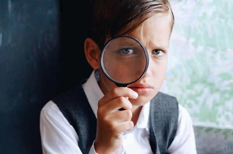Close-up portrait of boy holding magnifying glass