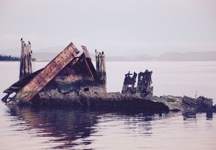 Abandoned Ship In Lake Against Sky