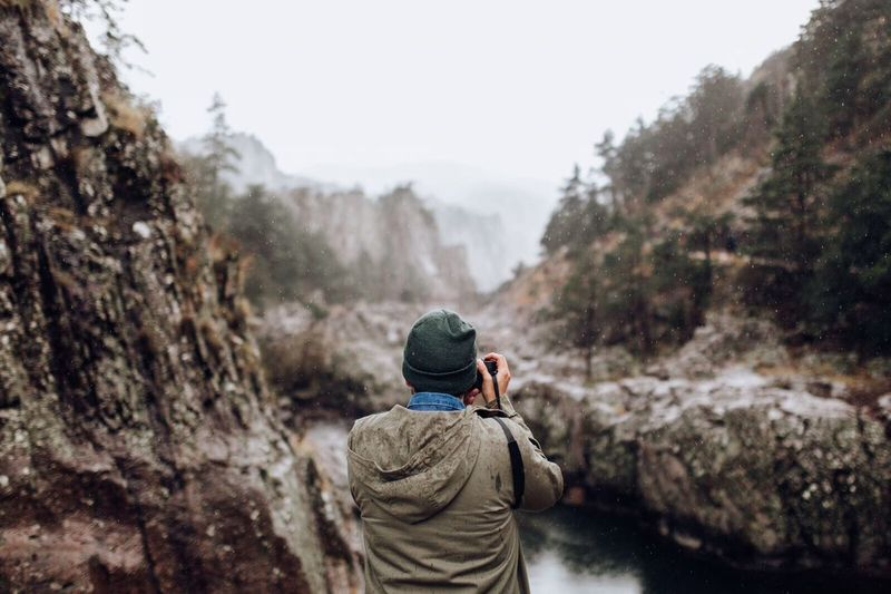 Rear View Of Man Taking Photographs Of Landscape