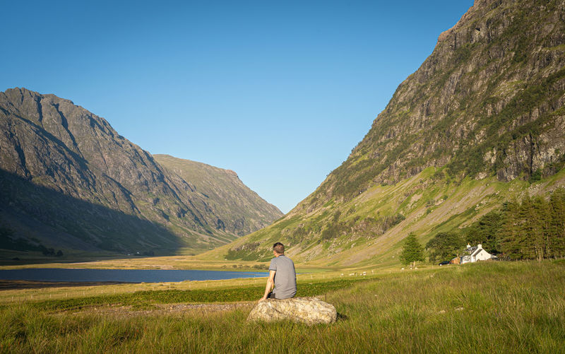 Scenic view in glen coe, scott. rear view of a man looking at beautiful nature and mountains