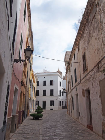 picturesque quiet empty typical street in ciutadella menorca with old traditional houses and a street lamp with blue cloudy sky Street Cobblestone Empty Minorca Tourism Building Exterior Architecture Built Structure Building Residential District Sky City Cloud - Sky Direction The Way Forward Nature No People Day Narrow Footpath Window Outdoors Transportation House Alley