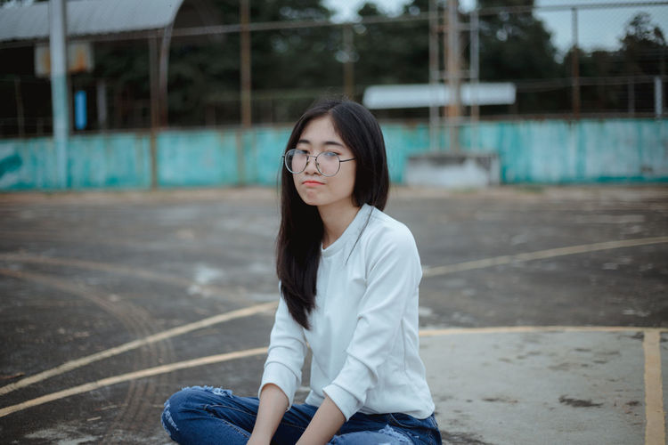 Young woman sitting on basketball court