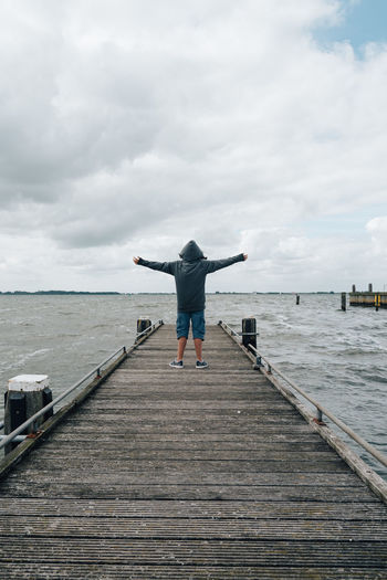 Rear View Of Teenager Standing On Jetty