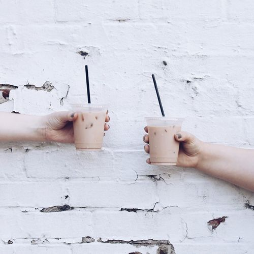 Cropped hands holding cold coffee against wall
