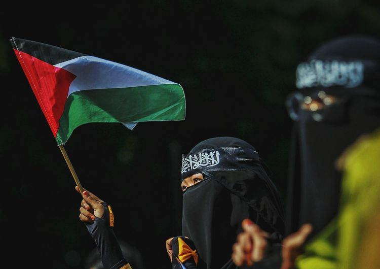 Woman in burka holding flag outdoors
