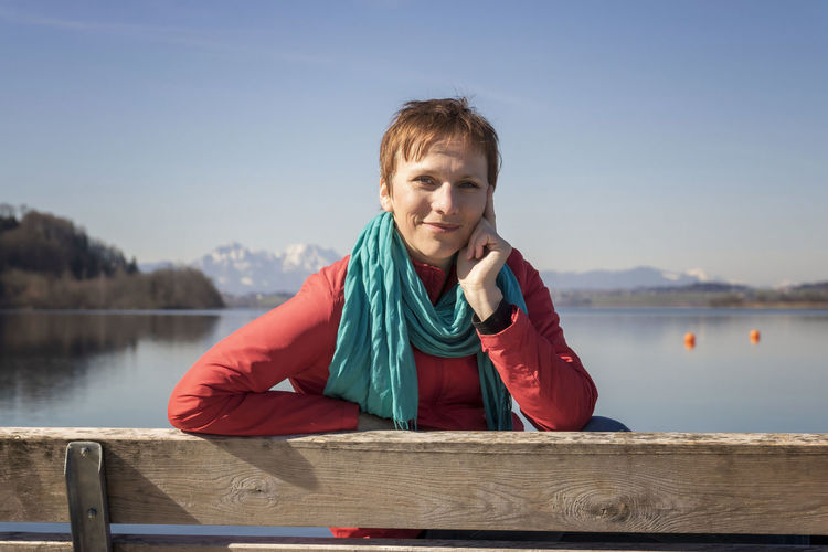 Portrait of woman sitting on bench against lake and sky