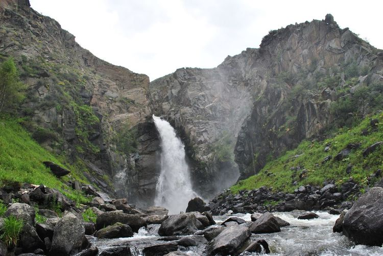 Scenic view of waterfall against rocky mountains
