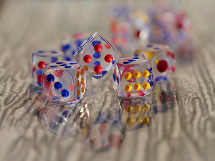 Close-Up Of Multi Colored Dice On Table