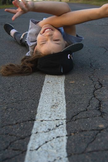 Portrait of young woman lying on road