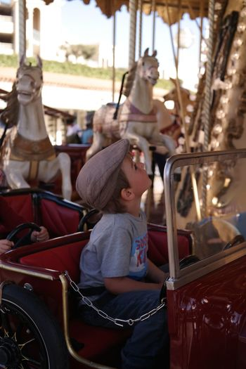 Rear view of boy riding carousel in amusement park