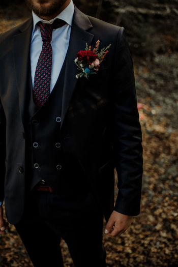 Midsection of bridegroom standing outdoors