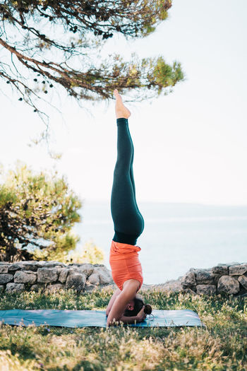 Side view of woman exercising against sky