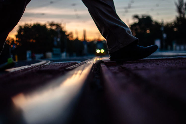 Low section of man crossing railroad tracks during sunset