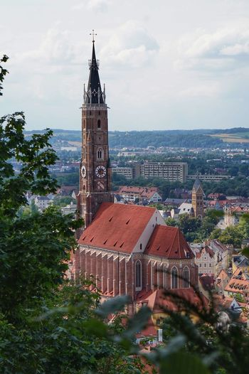 View of town by buildings and chuch against sky