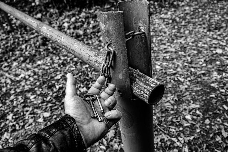 Cropped image of man holding keys by metal pole