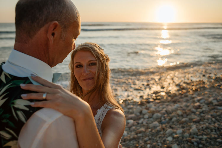 Midsection of wedding couple at beach against sky