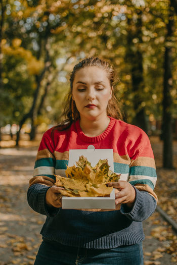 Beautiful woman holding autumn leaves standing at forest