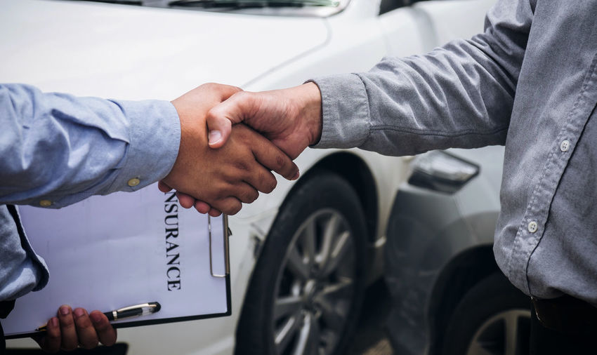 Midsection Of Men Shaking Hands After Buying Car Insurance