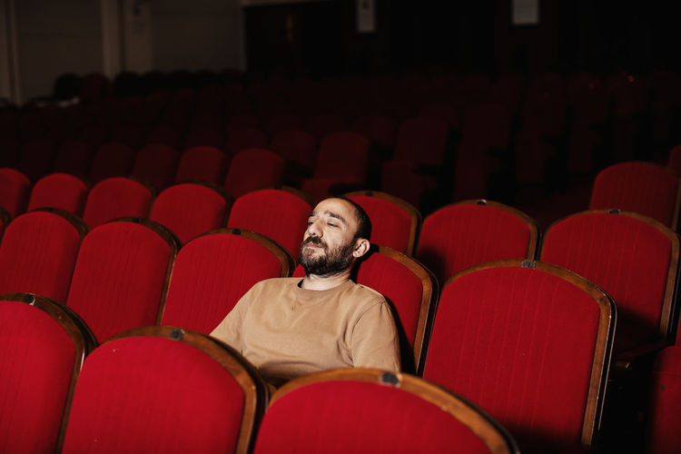 Seat Movie Theater Arts Culture And Entertainment Red Sitting Indoors  Chair Men Adult Leisure Activity In A Row Looking Lifestyles Auditorium Front View Film Industry Watching Contemplation Cinema Empty Teather Alone Loneliness Lonely