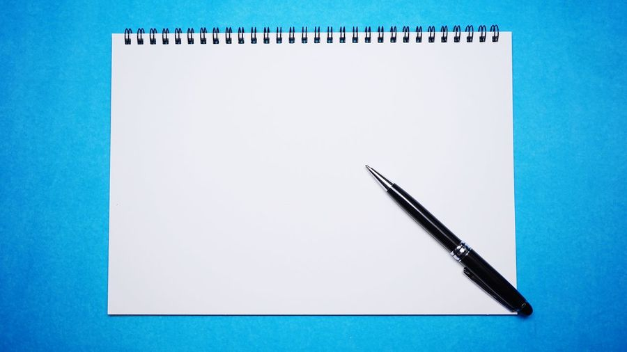High angle view of pen on table against blue background
