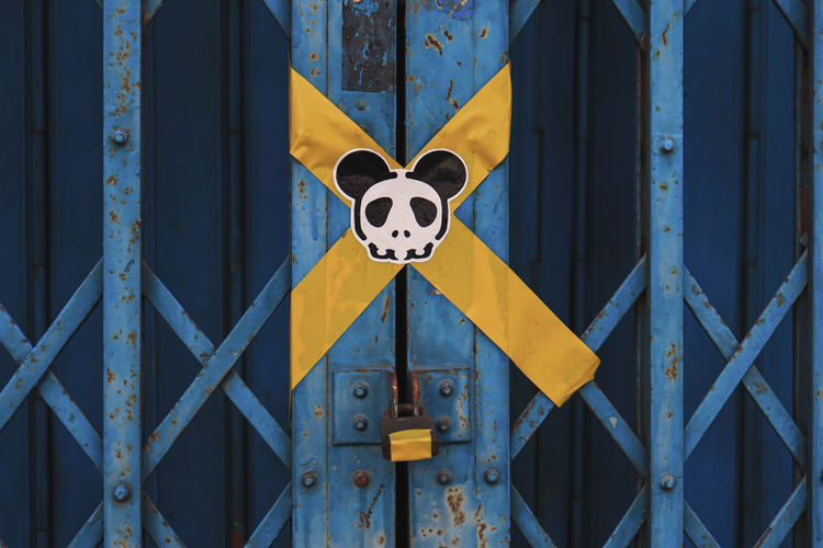Close-up of yellow sign on metal fence
