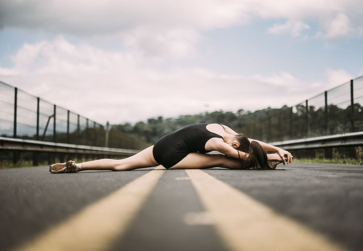 Surface level of young woman stretching on road