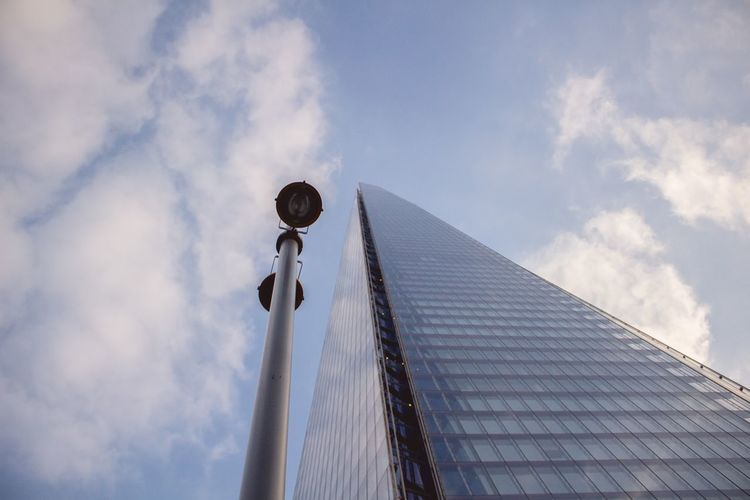 Low Angle View Of Shard London Bridge And Street Light Against Sky In City On Sunny Day
