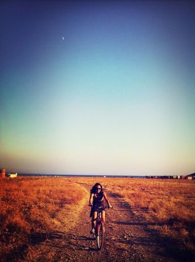Young woman cycling on dirt road against clear blue sky