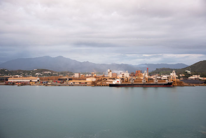 Noumea, New Caledonia: November 25,2016: Commercial dock, mountains and Pacific Ocean waters in Noumea, New Caledonia Container Container Ship Industrial Noumea Architecture Building Exterior City Cloud - Sky Commercial Dock Dock Dockside Freight Transportation Mountain Mountain Range Nature Nautical Vessel New Caledonia Outdoors Pacific Ocean Sea Ship Shipping  Sky Water Waterfront