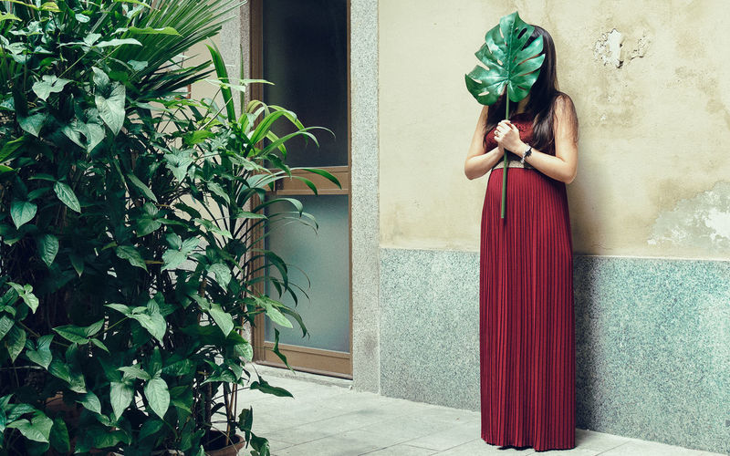Woman Holding Leaf While Standing Against Wall