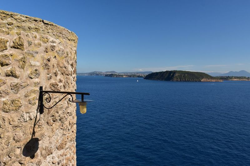 Scenic view of sea and islands with clear blue sky in the bay of naples from castello aragonese