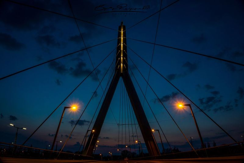 Low angle view of illuminated bridge against sky at dusk
