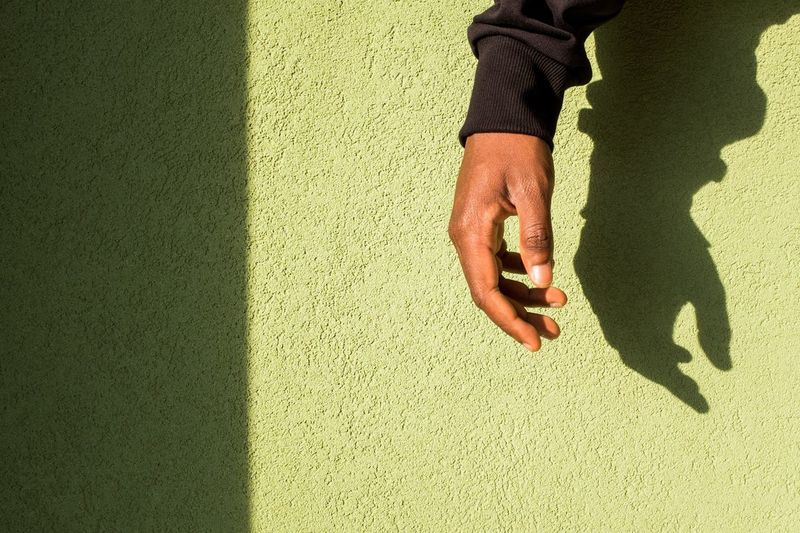 Midsection of man with shadow on hand