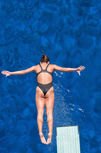 Directly above shot of woman jumping in swimming pool