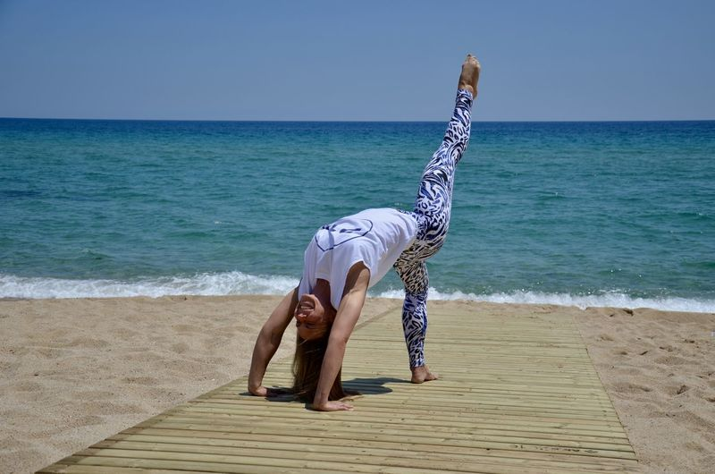 Full Length Of Woman Exercising By Sea