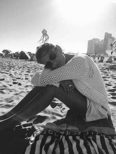 Full length of boy sitting on beach against sky