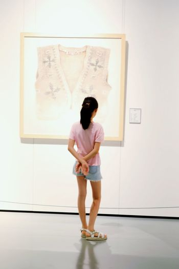 Rear view of woman standing against wall in museum