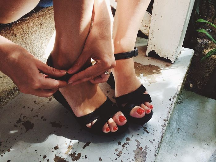 Low Section Of Woman Fastening Sandals On Steps