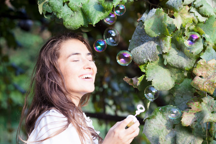 young woman having fun with bubbles Bubbles Fun Happiness Blowing Casual Clothing Day Emotion Face Hairstyle Happiness Leisure Activity Lifestyles Nature One Person Outdoors Party Plant Portrait Real People Side View Smiling Soap Women Young Adult Young Women
