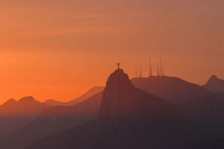 Cristo redentor at sunset Cristo Redentor Rio De Janeiro Brasil Sunset Mountain Top Mountain Sky Red Sky Politics And Government Sunset Beauty Dawn Place Of Worship Fog Ancient Silhouette Mountain History