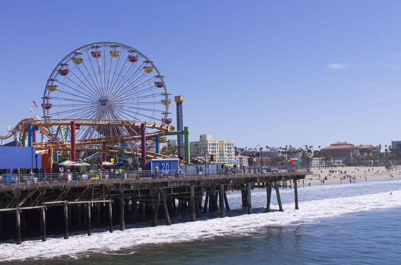 Amusement Park Rides At Beach Against Clear Sky